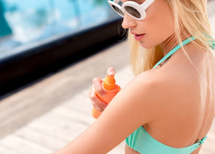 woman in a turquoise bikini and white sunglasses spraying sunscreen on her arm
