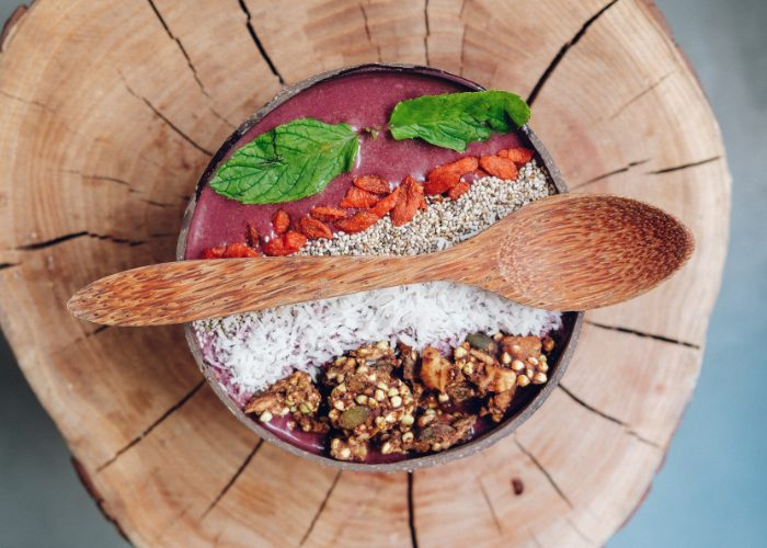 healthy vegan gluten free breakfast bowl including coconut flakes, chia seeds, goji berries, and a nut mix on a wooden base, in a wooden bowl with a wooden spoon