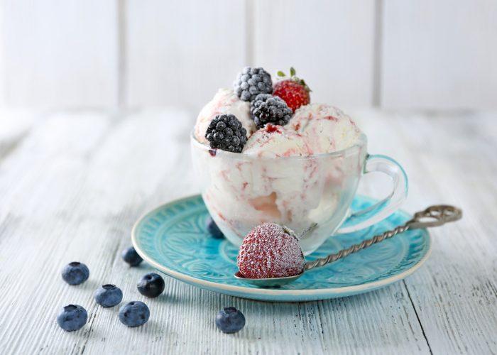 vegan gluten free vanilla ice cream in a clear teacup, on a blue dish, with berry toppings