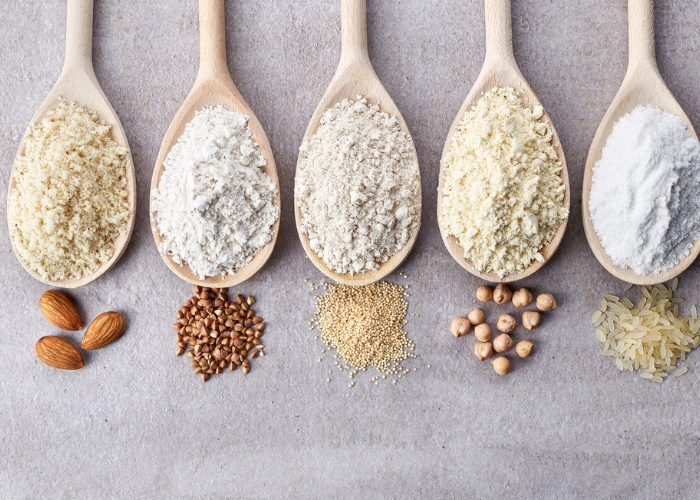 five types of gluten free flours on wooden spoons