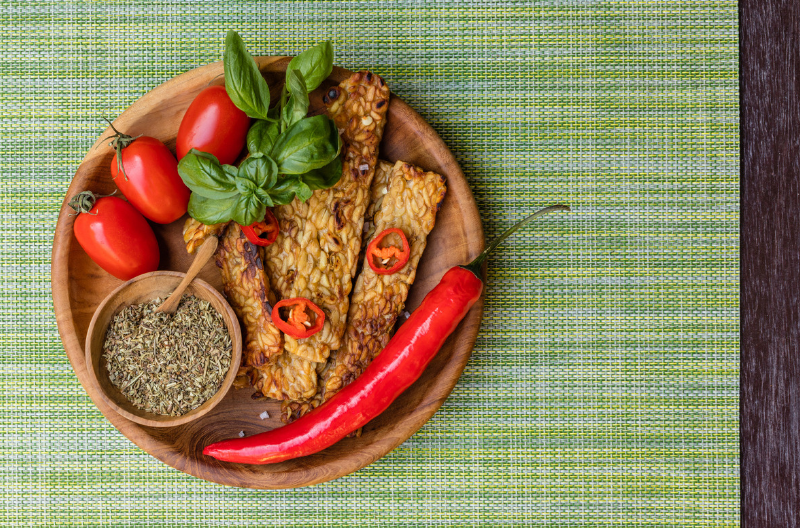 Fried tempeh on a wooden plate with fresh cherry tomatoes, red chili pepper, garnished with basil leaves and cut red chili