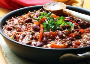 a bowl of soya mince chili con carne with a wooden spoon on the side