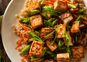 a healthy stir fried tofu dish with vegetables and rice on a plate