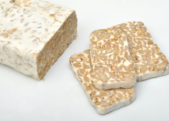 a block and three slices of tempeh, a well known vegan meat alternative