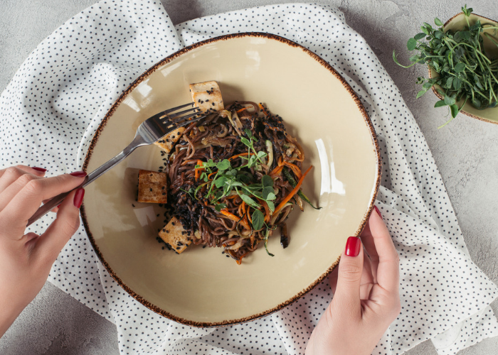 woman holding a fork with a vegan dish of stir fried buckwheat noodles and tofu