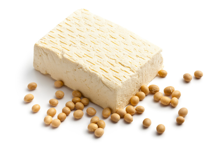 a block of tofu and soy beans on a white table