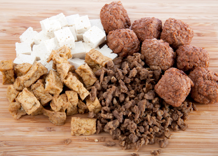Four different types of vegan meat substitutes on a table, including tofu and seitan