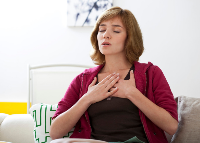 Woman with both hands on her chest practicing 4-7-8 breathing technique at home