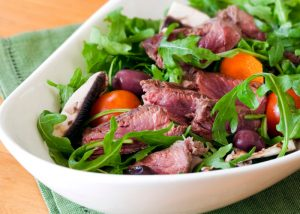A dish with green salad and roast beef