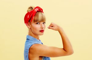 "Strong, blonde woman in blue denim sleeveless top and a red headband flexing her biceps against a pale yellow wall, emulating the ""We Can Do It!"" poster from World War II"