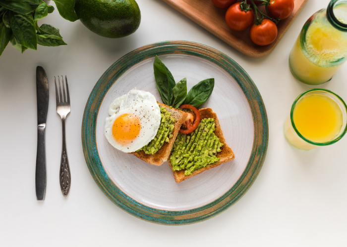 Plant-based breakfast of avocado on toast with a sunny side up egg on a plate, with a fork, knife and glass of orange juice beside it