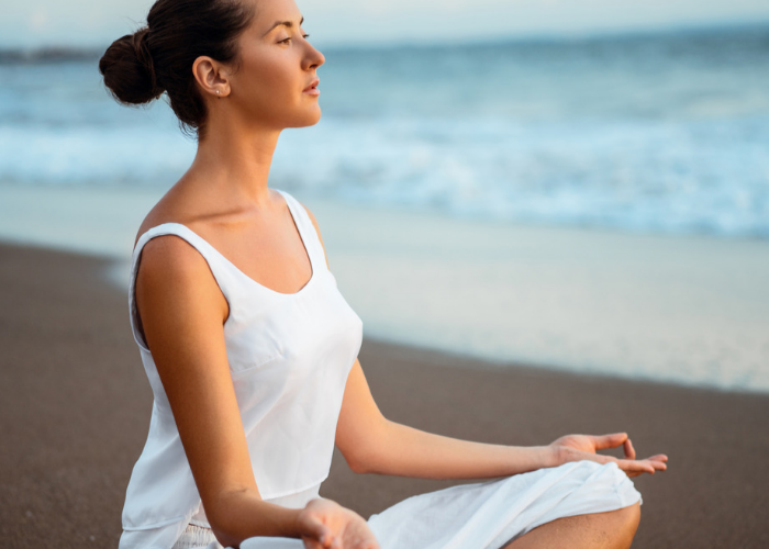 Woman sitting on the sand with the sea in the background in the middle of a meditation practice