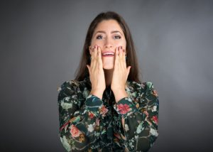 Woman with her hands on her face doing face yoga method exercises