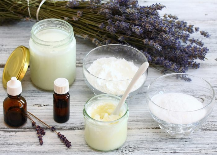 Homemade natural deodorant ingredients in jars and dishes on a wooden table with a bunch of lavender in the background