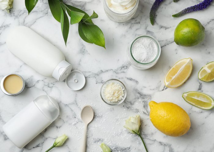 Homemade natural deodorant ingredients such as lemon, lime, lavender, baking soda, and bottles on a marble table