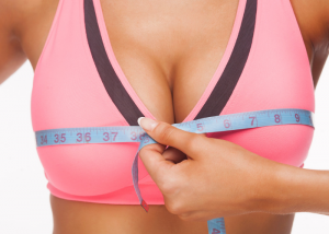 Woman in pink sports bra with a measuring tape measuring her bust size to find the best sports bra for her