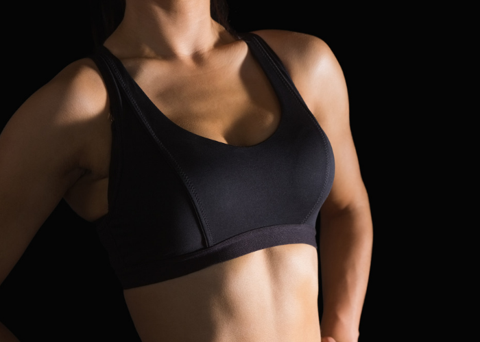 Woman in a plain black sports bra standing against a black background