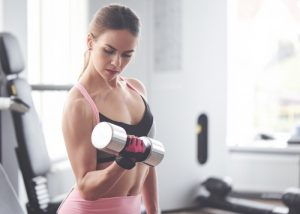 fit woman in pink and black sports bra doing bicep curls in the gym