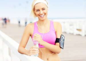 Blonde short-haired woman smiling in light purple sports bra with earphones, an iPhone, and a water bottle after a run