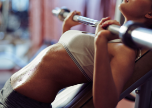 Woman in a white sports bra sweating from lifting weights in the gym