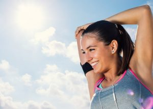 Woman in grey and pink sports bra smiling and doing arm stretches