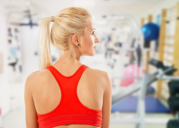 Blonde woman wearing red sports bra in the gym