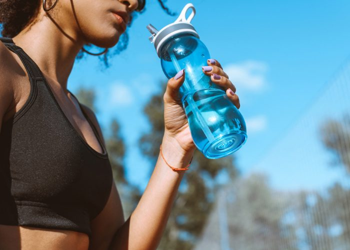 Woman in black sports bra drinking from a blue water bottle outdoors