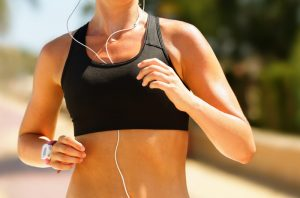 Woman jogging outdoors in black sports bra and with earphones