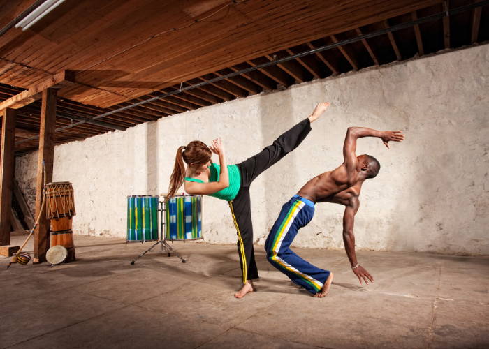 A sparring couple practicing the  Brazilian martial arts, Capoeira. A woman is performing a high kick, and a man is trying to lean back to avoid the kick.