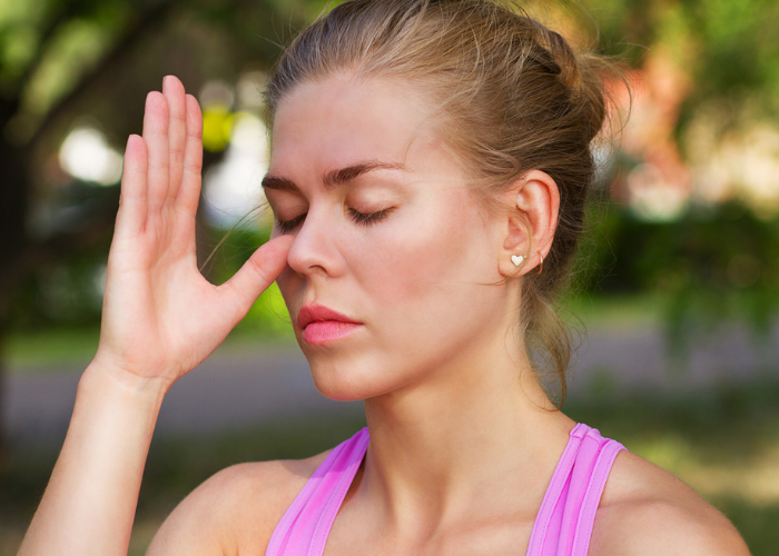 Woman with eyes closed and thumb by the side of her nose practicing nose breathing techniques