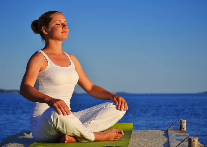 Woman sitting outdoors by the sea on a green yoga mat doing breathing exercises