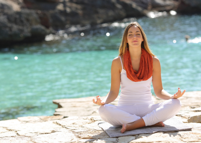 Woman wearing white clothes sitting by a river in a meditation pose doing breathing exercises