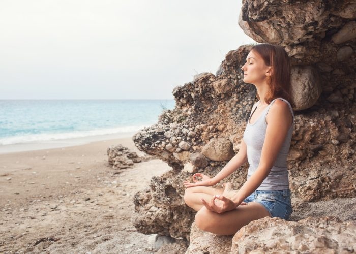 woman sat on a rock by the beach with eyes closed practicing breathing exercises