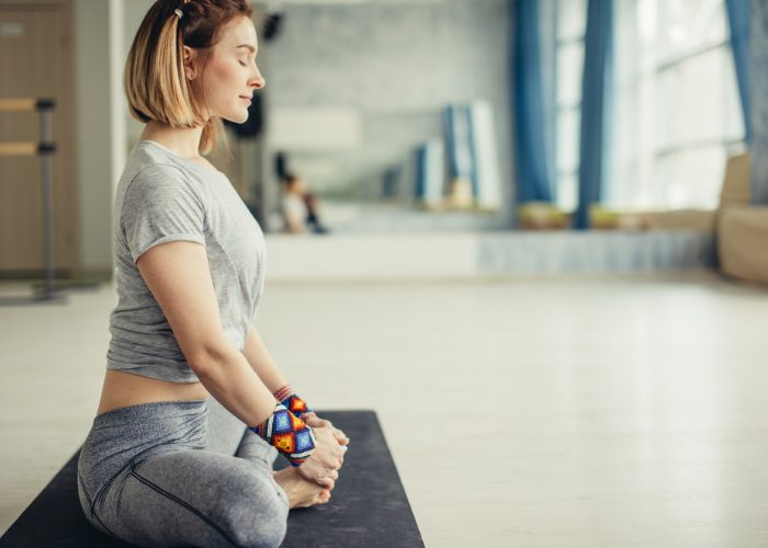 Woman sitting on a yoga mat with eyes closed meditating