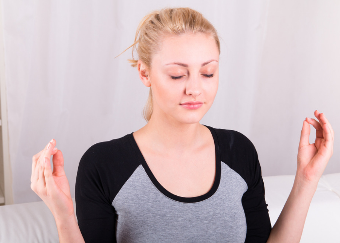 Blonde woman with eyes closed with hands in mudra doing breathing exercises