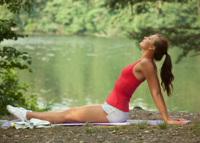Woman sitting outdoors in a park stretching and doing breathing exercises