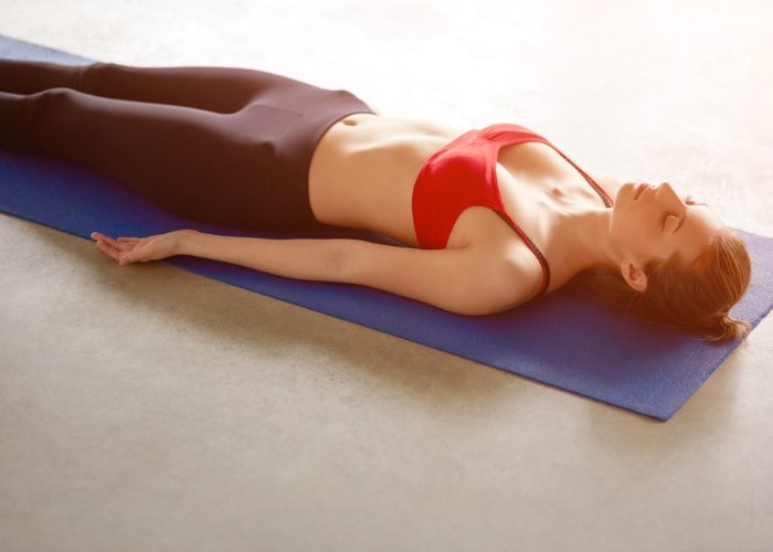 Woman in gym gear, lying on a yoga mat with her eyes closed practicing breathing exercises