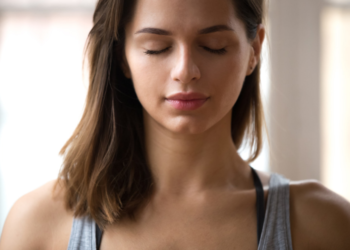 Woman with eyes closed practicing breathing techniques