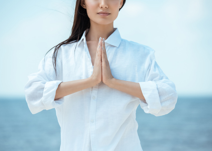 Woman in a white shirt standing by the seaside practicing breathing exercises