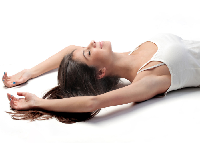 woman laid out on the ground practicing breathing exercises for sleep