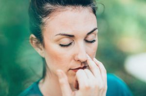 Woman with eyes closed and finger next to her nose doing breathing exercises