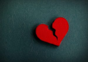 Cut out shape of a red broken heart against a dark grey background