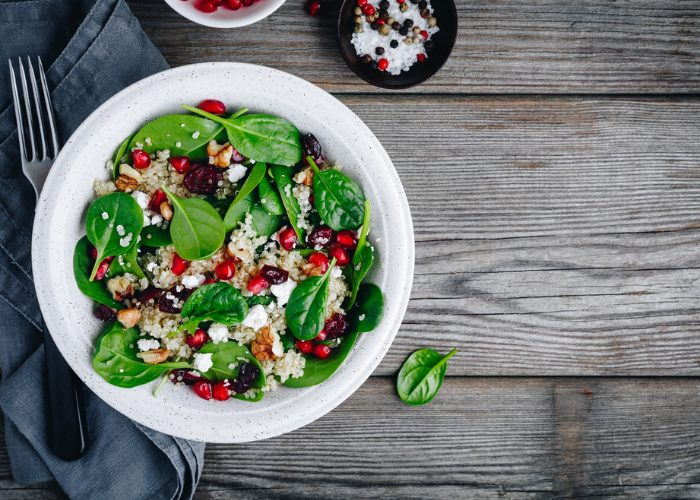 Plant-based Buddha bowl with spinach, grains, pomegranate seeds, set on a wooden table