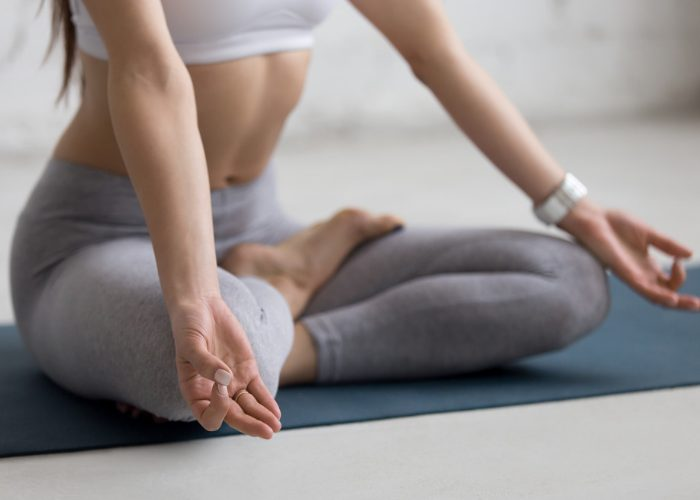 Woman at home on a yoga mat with hands in mudra practicing breathing exercises for anxiety