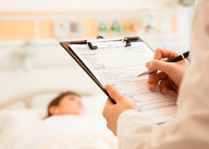 A doctor filling out the medical chart of a patient in the hospital bed