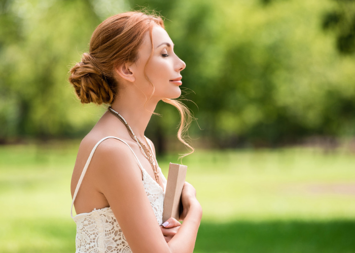 Woman with her eyes closed in a park outdoors, holding onto a book, doing breathing exercises