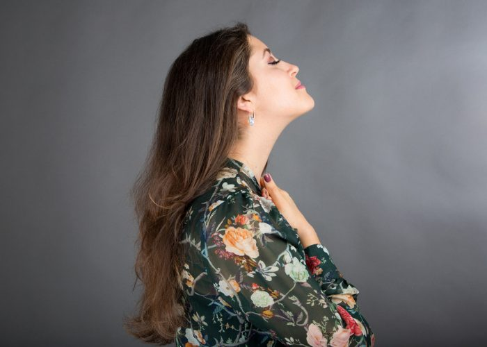 Woman stretching her neck by tilting her head up doing in the middle of a face yoga practice