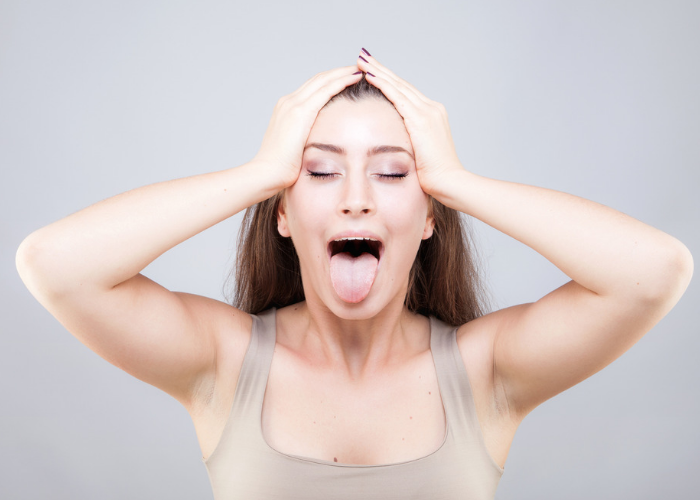 Woman doing face yoga with her eyes closed and face open wide with tongue sticking out
