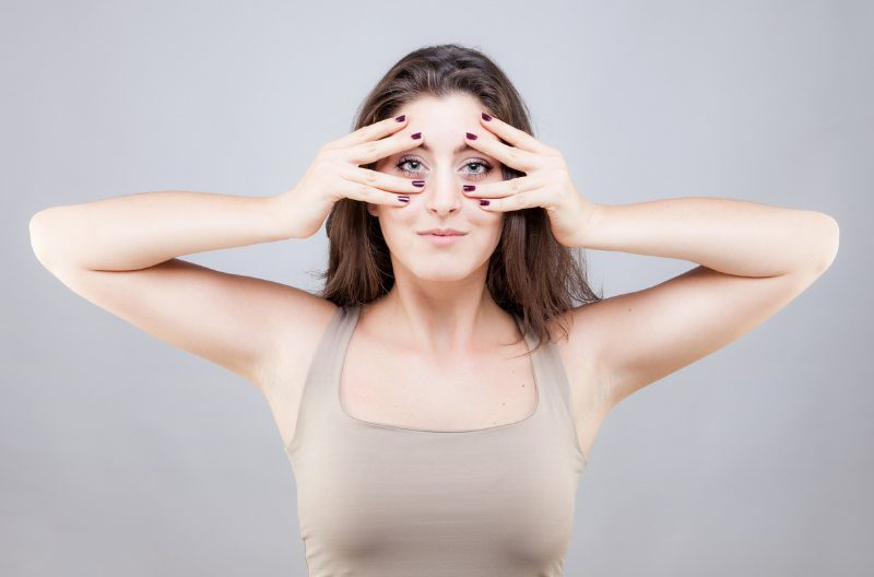 Woman doing face yoga exercises, massaging her face