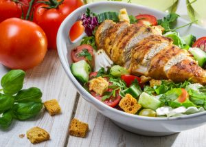 A bowl of salad greens and chopped tomatoes and cucumbers topped with grilled chicken breast and croutons